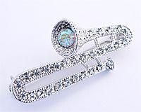Se mere om Broche af sølvfarvet trombone/basun med hvide sten i web-butikken