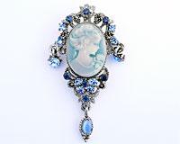 Se mere om Broche i sølvfarve med ovalt motiv af dame i lyseblå farver i web-butikken