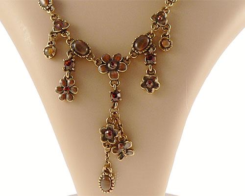 Se mere om envy halskæde i messingfarve med blomster i brunlige sten i web-butikken